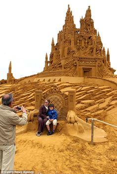 Visitors pose for a picture in front of one of the amazing sand castles
