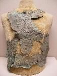 In the Museum of Teruel Inventory#232228 Archaeological Wing Military Objects of War Repousse on Bronze 48cm high 21cm wide 1mm Thick Found in a grave vault 2 Km Southwest of San Antonio de Calaceite in 1903 near two ancient villages dating to approximately 550-501 BC  Museo de Teruel 23228 Arqueología Objetos bélicos y militares; Mundo funerario; Indumentaria. Complementos Coraza Bronce Repujado Altura = 48 cm; Anchura = 21 cm; Grosor = 1 mm Excepcional ejemplar de coraza, realizada sobre…