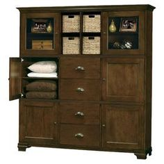 Pairing chic style with versatile design, this storage essential brings effortless organization to your home.    Product: Armoire  Construction Material: Hardwood and veneers      Color: Saratoga and antique brass    Features:      Two doors with plain glass and four doors with inset panels    Four flat panel drawers  One cross storage shelf with four woven baskets