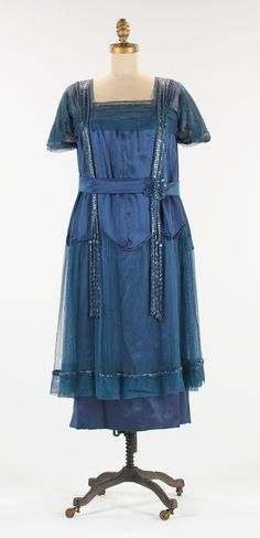"""Evening Dress: ca. 1918, American, silk. """"The lines of this evening dress represent the transitional shape found during the teens to the early 1920s. Executed in an appealing shade of blue, its shorter length and tubular shape presage the silhouette to come. While many examples of 1920s dresses are extant, dresses from this era are more difficult to find."""""""