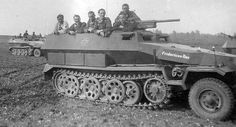 """The crew of an SdKfz 251/10 Ausf. C Schützenpanzerwagen, named """"Fridericus Rex"""" after Friedrich II, King of Prussia, poses for the camera on the front. The 3.7 cm PaK 36, missing its gunshield, can be seen mounted atop the driver's cabin."""