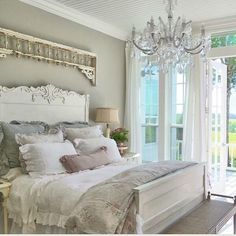 pastel colored shabby chic bedroom with a crystal chandelier
