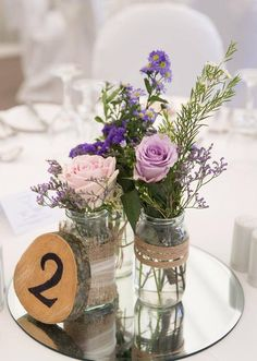 Jam Jar Arrangement: Lavender Limonium, Purple Statice, Purple September, White Wax Flower, Sweet Avalanche, Cool Water Roses on a mirror plate.