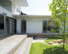建物と生け垣、木板塀で囲われた庭