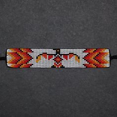 These beaded bracelets were designed and hand-loomed by crafter Charlotte Disbrowe. Charlotte is Anishinaabe from Winnipeg, Manitoba. She is from the Algonquin Ojibwe peoples. Learning from her Mom at a young age, she continues the tradition of loom beading. Inspired by her cultural heritage she designs her artwork on her bead loom using seed beads. This bracelet measures about 13-1/2 long, including the ties, and the beaded band is about 6-1/4 long and 1-1/8 wide.