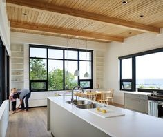 white walls balanced by natural wood ceiling & floors.  dark window frames
