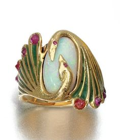 Gold and opal ring designed as two opposing swans decorated with green enamel and set with circular-cut rubies, embracing an oval opal, circa 1900