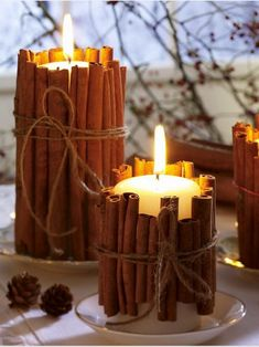 cinnamon stick candles wrapped with twine atop china saucers