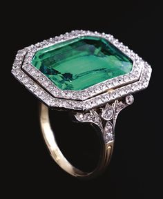 VERY FINE EMERALD AND DIAMOND RING, CIRCA 1910. The step-cut emerald weighing approximately 9.50 carats set within a double frame of circular-cut diamonds, highlighted by similarly-set shoulders, to a pierced scroll gallery,