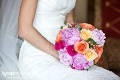 pastel old world themed wedding, bright pinks and oranges paired with pastel colored flowers bouquet, bride in classic white wedding gown.
