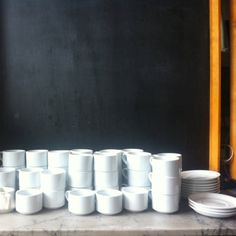 stacked simple coffee cups at universal cafe. sitting in front of giant chalkboards, framed in warm wood, hanging like sliding doors off of industrial beams. so many textures... so beautiful and simple.