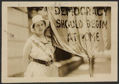 """Mrs. Susanna Morin Swing [holding banner, """"Democracy Should Begin at Home."""" Harris & Ewing, Washington, D.C., 1917. Women of Protest: Photographs from the Records of the National Woman's Party, Library of Congress Manuscript Division."""
