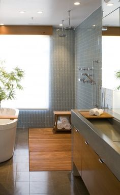 Vertical use of feature tile on the walls paired with a simple flooring tile softened by timber. Yes!