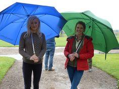 Amy and Hannah hiding from the rain under their umbrellas.