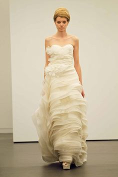 Vera Wang Strapless micro flange bodice modified ball gown with silk organza and mixed lace wave flange skirt. Blossoming hand rolled organza petal corsage at waist.