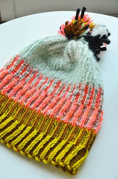 Gather a colorful selection of DK weight yarns for this two-color brioche hat. Begin at the bottom with brioche ribbing in the round. When you're ready for something new the ribbed columns syncopate so the knits are purled and the purls are knit. Swap colors freely for a super striped effect and don't forget to top it off with a pom pom!