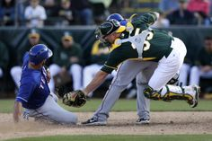 Oakland Athletics catcher Chris Gimenez, right, leaps past Texas Rangers' Jose Felix, center, as he tags out Alex Castellanos, left, caught trying to steal home during the eighth inning of a spring training baseball game Saturday, March 1, 2014, in Phoenix. (AP Photo/Gregory Bull)