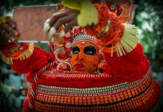 Theyyam artist getting ready - A final check in the mirror before this amazing performance began.  Theyyam art form is practiced in the southern state of Kerala Kannur district and surrounding areas.