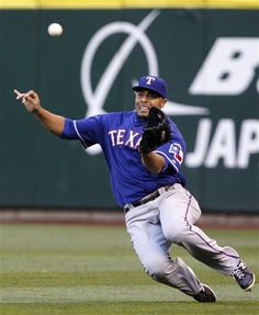 Texas Rangers right fielder Nelson Cruz slides toward a shallow fly ball from Seattle Mariners' Miguel Olivo with the bases loaded in the fourth inning of a baseball game Friday, July 13, 2012, in Seattle. Cruz made the catch to end the inning. (AP Photo/Elaine Thompson)