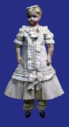 1880 Doll Culture: English Medium: wax, cotton, wool Wax doll with rag body. Dressed in white cotton lace trimmed chemise knickers and waist length petticoat, flannel petticoat and dress of fine pink wool trimmed with embroidery.