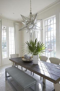 White and blue cottage dining room features a Moravian XL Star Pendant illuminating a modern wood and metal dining tables lined with beige mixed dining chairs as well as a blue nailhead bench surrounded by windows dressed in white French pleat curtains accented with blue trim.