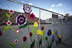 chain link #fence with crocheted flowers - how adorable is that?  Let's go yarn bombing!!