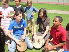 students playing drums made from wood working.