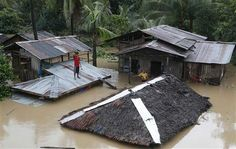 """SUPER TYPHOON VICITMS FLEE AGAIN AS RAINS FLOOD SOURTHER PHILIPINES A RESIDENT STANDS ON THE ROOF OF HIS HOME THAT IS SUBMERGED IN HEAVY FLOODING BROUGH BY TROPICAL DEPRESSION """"AGATON"""" IN BUTUAN CITY ON THE SOUTHER PHILIPPNE ISLAND OF MINDANAO ON 1/21/14"""