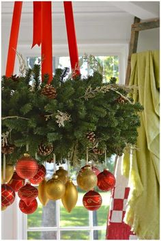 a gorgeous Christmas chandelier of evergreens, gold and red ornaments and red ribbons is amazing for holiday decor - DigsDigs Christmas Kitchen, Noel Christmas, Christmas Wreaths, Christmas Ideas, Modern Christmas, Christmas Christmas, Christmas Chandelier, Gold Christmas Decorations, Red Ornaments