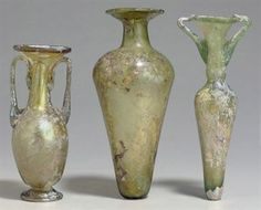 3 ROMAN GLASS FLASKS C. 3RD-4TH CENTURY A.D. All free-blown: 1 olive-gold, w/ a piriform body, pinched flaring foot + long cylindrical neck, the wide funnel mouth w/ the rim folded in, w/ twin pale-green handles; 1 olive-green, w/ wide shoulders, tapering to the rounded base, w/ a cylindrical neck + wide funnel mouth, the rim folded in; 1 pale green in color, the body w/ rounded shoulders tapering to the base,  a long cylindrical neck + funnel mouth, the rim folded in, + twin angled handles…