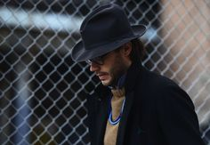 Justin Doss in a black wool overcoat with split peak lapel detailing.  High fashion cowboy western.  Tommy Ton Photo