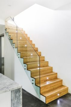 Exquisite Hall Design With Modern Wooden Staircase Design And Glass Balustrade Lightened By Modern Stairs Lamps At Montreal Duplex