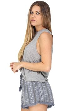 Grey jersey muscle tank top featuring oversized arm holes. Pair this simple tank with jeans for the perfect minimalist inspired look or dress it up with a statement necklace and heels for drinks with your friends!