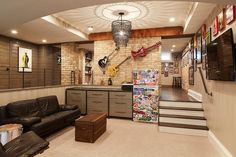 Well appointed sunken man cave features a black chain tiered chandelier illuminating a black leather sofa placed facing a trunk coffee table and a wall mount television mounted beneath framed art.