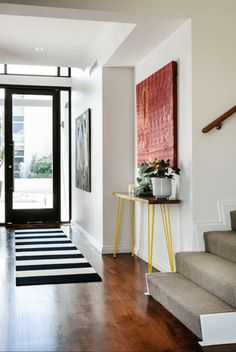 white modern foyer with rust red wall art, pantone dusty cedar, dusty red, barn red, faded red, brick red