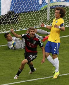 Germany's Thomas Mueller (C) celebrates past Brazil's David Luiz and goalkeeper Julio Cesar after scoring a goal during their 2014 World Cup semi-finals at the Mineirao stadium in Belo Horizonte July 8, 2014. REUTERS/David Gray