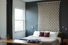 white bedroom with dark grey accent wall; black window curtain; light bedding; large macrame wall hanging as headboard
