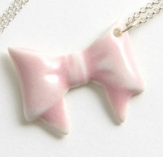 BOW NECKLACE - A cute bow necklace, handmade in the UK with love and care.    The glazed porcelain bow comes is coloured pretty pastel pink, measures approximately 3.5cm across and sits on a 55m sterling sliver chain. www.lumleylocket.com