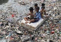 Des enfants jouent au milieu d'une rivière encombrée de détritus dans un bidonville de Djakarta (Indonésie), le 19 septembre 2012. | ENNY NURAHENI / REUTERS