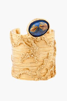"""YVES SAINT-LAURENT //  LARGE ARTY OVALE CUFF    Textured gold tone logo-embossed cuff with blue oval glass embellishment. Molten finish. Approx. 2.5"""" width, 7"""" circumference. Shell: 100% brass. Contrast: 100% glass. Made in Italy."""