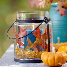 Make a bold fall statement with contrast. The blue and orange hues in this centerpiece bounce off each other; the yellow beads in the bottom soften the scheme. Adhere leaves to the outside of a vase filled with your choice of stones and candle. Surround with miniature pumpkins to complete the look.
