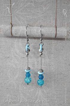 Réalisation [ Fait-Main ] avec du fil aluminium (Ø2mm), deux perles de verre craquelées et une  perle tibétaine, ainsi qu'une perle d'acier inox et un anneau d'aluminium laqué. Les crochets d'oreilles sont en acier inoxydable ainsi que la chaîne. Petites boucles d'oreilles ou boucles d'oreille à assortir avec tenue et maquillage, selon l'envie. Facile à mettre et enlever, la boucle d'oreille est légère et se dandine au gré des mouvements, avec de petits tintements agréables qui permettent…