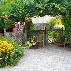 """This couple built an arbor across their once barren property giving the house a """"front"""" and """" backyard,"""" had the old driveway removed, installed pavers in the front, and over the years put in garden beds. 