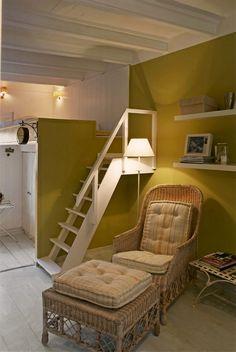 Por la escalera de madera se sube al dormitorio en el altillo. Ideal para personas solteras que quieren vivir en el corazón de Barcelona.