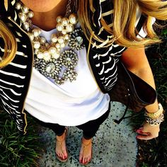 Striped vest, white tee, skinny jeans, sandals, and layered statement necklaces.