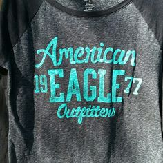 """Long Sleeve AE Baseball Style Tee Long Sleeve, American Eagle, Baseball Style Tee. Size Large. 57% Cotton, 43% Polyester. Teal graphic writing, sleeves are black, middle of tee, dark gray. When laying flat, from top of shoulder to bottom of the tee in front is 25"""", across chest from armpit to armpit is 19"""", sleeve length: 28"""". No rips, tears, flaws, or defects. Comes from a smoke free home. American Eagle Outfitters Tops Tees - Long Sleeve"""
