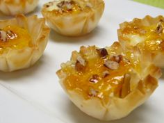 Mini filo shells, hunk of brie, dollop of apricot jam, sprinkle of pecans. Bake @ 350 for 15 mins.