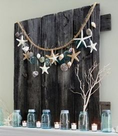 A pallet mounted over the fireplace with a ocean and beach theme