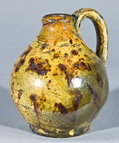 "$ 2645 Miniature Glazed Redware Jug, New England origin, early to mid 19th century, small-sized ovoid jug with rounded foot and ribbed handle, decorated cream-colored slip and daubs of manganese under a clear lead glaze. Attractive green, orange, cream, and brown coloration. Desirable size. Wear to rim. Light wear to handle. Small spots and thin separations where glaze separated on jug's surface. H 4""."