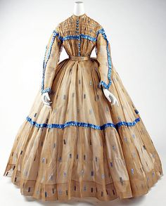 Embroidered silk sheer, probably American, 1860-65; high bodice of soft gathers, band collar, yoke shirred front and back, narrow sleeves, pleated skirt with self hem. The dress is trimmed in ruching on the yoke, armscye, sleeves, skirt. MET